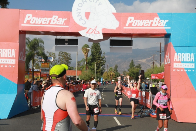 Natalie Brown crossing the finish line at the Canyon City Marathon in 2014 with her first BQ.